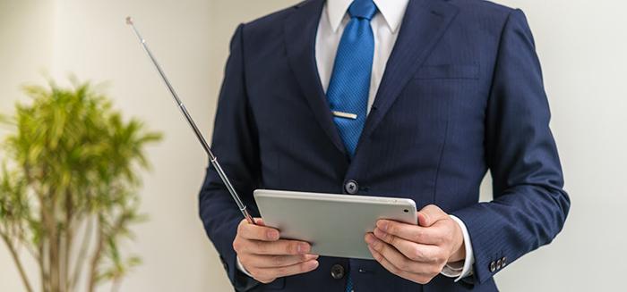 タブレットと指示棒を持つ男性